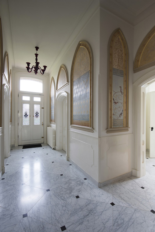 Twelve restored painted panels in the entrance. <p>For some of these the damage to the original trompe l\'oeil painted curtains was beyond restoration,<p> they were replaced by new images of birds and fragmented rose branches.
