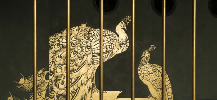 Abe's peacocks, two monumental statues of gold-leaf behind brass vault bars.