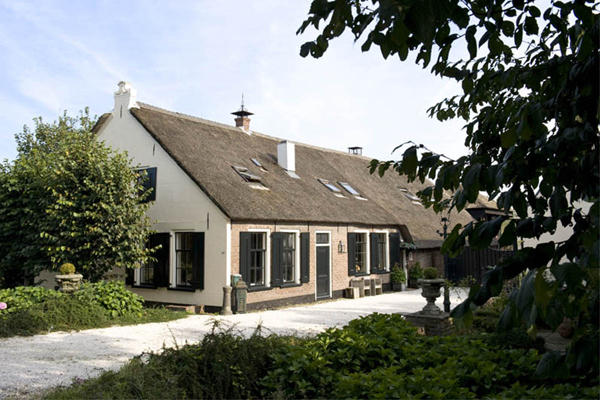 A monumental historic farmhouse on the banks of a small meandering river just outside of Amsterdam